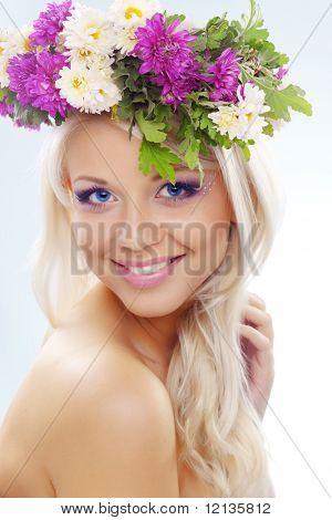 Beautiful youg girl wearing floral wreath closeup