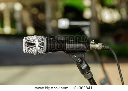 Closeup view of microphone detailed head against blurred outdoor background