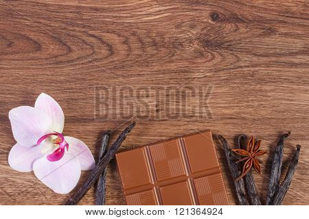 Milk chocolate, fragrant vanilla sticks and blooming orchid, copy space for text