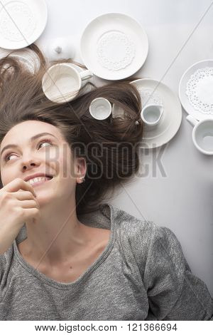 Brunette women lies on her back on a white background in dish: smiling, earring, happiness, flowing hair
