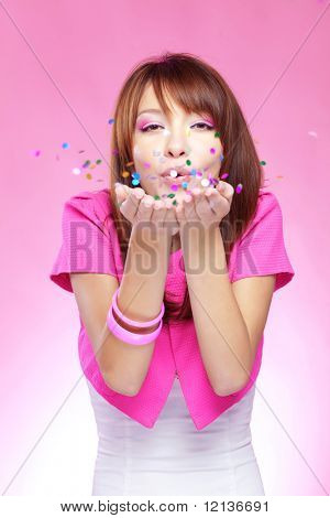 Portrait of young cute girl blowing confetti at holiday party, studio shot