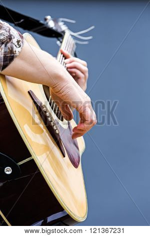 guitarist hands playing acoustic guitar closeup