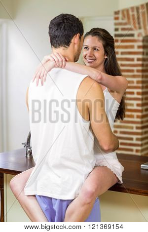 Romantic young couple cuddling on kitchen worktop