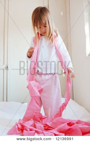 Portrait of child playing with pink toilet paper
