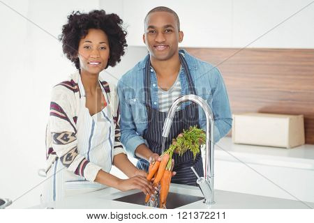 Happy couple washing carrots in the kitchen