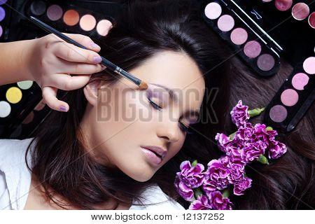 Make-up artist making eye visage to beautiful woman
