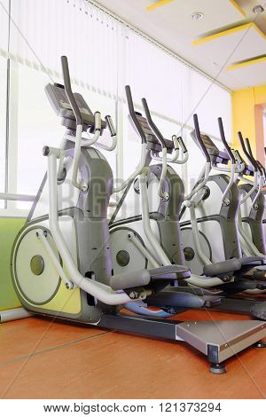 Elliptical cross trainer in a row in a gym