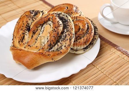 Still life with two sweet buns with poppy seeds on the table.