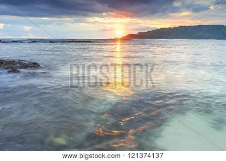 Natural beach and wave with orange sunset background