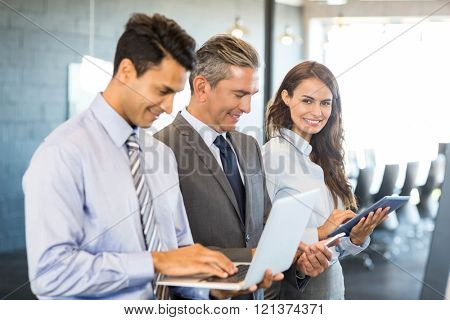 Businesspeople standing in a row and using mobile phone, lap top and digital tablet in office