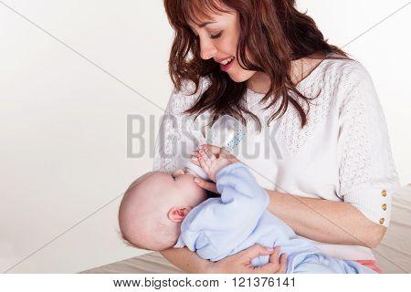 mom feeds the baby newborn little bottle