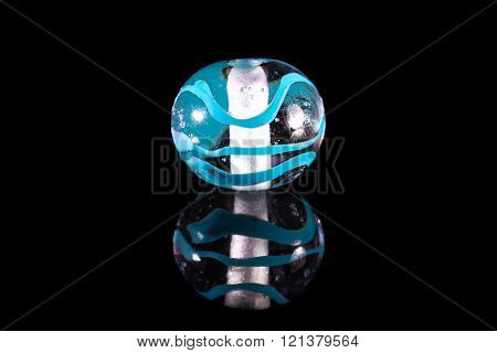 Clear blue glassy bead with reflection