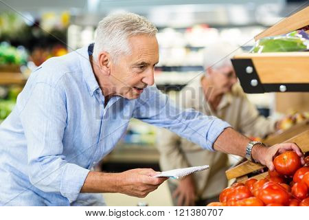 Smiling senior man with list buying apple at grocery shop