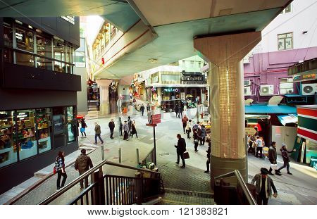 Many People Walking Under The Bridge In Busy District With Tall Buildings And Maze Of Streets