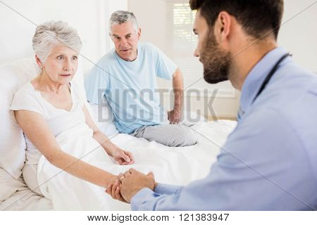 Handsome nurse holding hand of mature woman at home