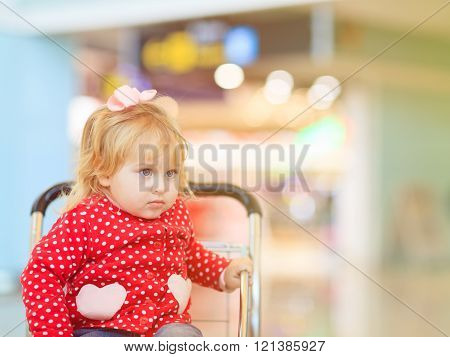 little girl on luggage cart in the airport