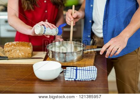 Woman pouring milk while man stirring the batter in pan