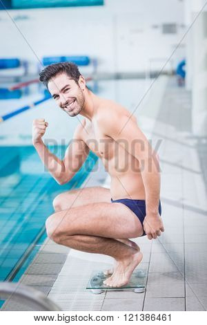 Fit man triumphing on the weighting scale at the pool
