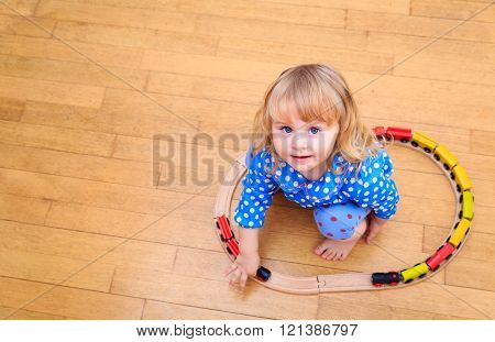 little girl playing with trains indoor