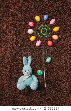 Abstract Flower With Colored Eggs On The Carpet.easter. Flat Lay.toy Rabbit