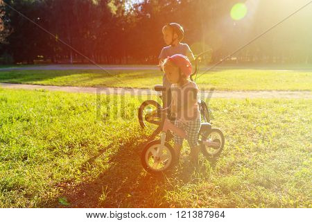 little boy and girl riding bikes at sunset