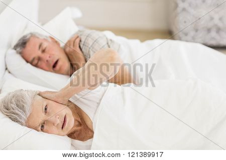 Awake senior woman in bed covering her ears while her husband is snoring