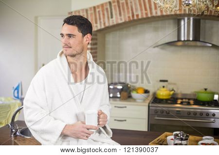 Young man sitting on kitchen worktop and holding a cup of tea
