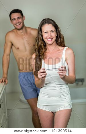 Portrait of happy couple smiling after checking pregnancy test results