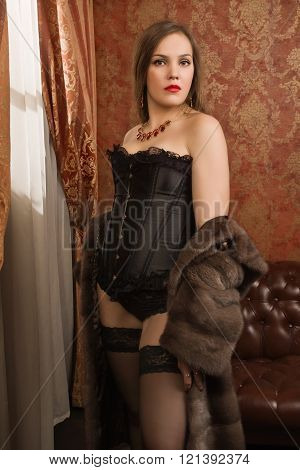 Fashion sexy brunet curly woman in lace lingerie and stockings at bedroom