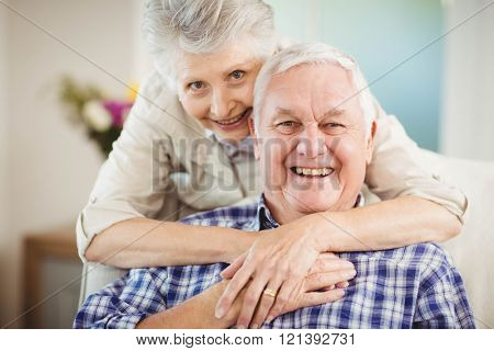 Portrait of senior woman embracing man in living room