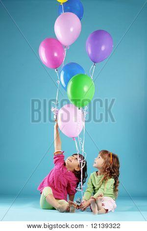 Niños felices con globos de aire colorido sobre azul
