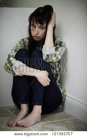 Female Victim Of Domestic Abuse Sitting On Floor