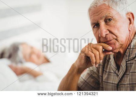 Portrait of worried senior man sitting on bed in bedroom