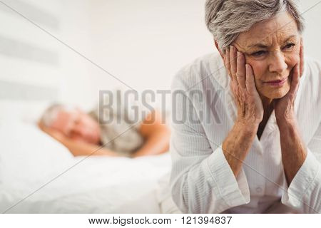 Worried senior woman sitting on bed in bedroom