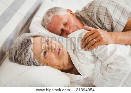 Senior man sleeping while woman still awake on bed in bed room