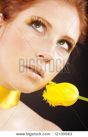 Beautiful fashion model with red hair and yellow flowers on black background