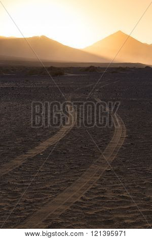 Wheel tracks in sand in dramatic landscape.
