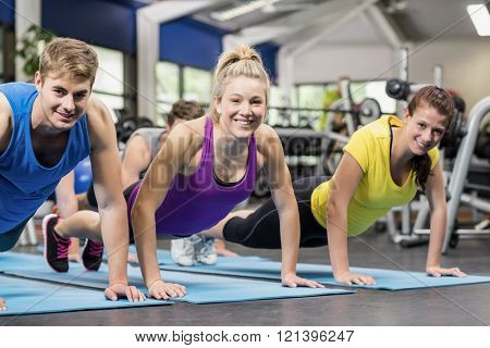 Fit people in plank position in gym