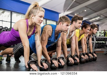 Fitness class in plank position with dumbbells in gym