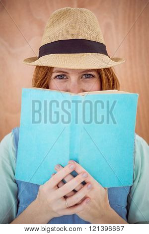 blue eyed hipster woman, wearing a trilby and looking over the top of a book