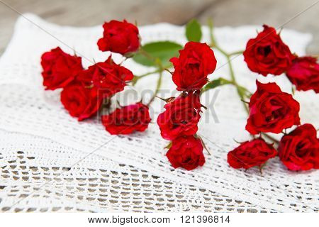 red rose petals on white lace on wood