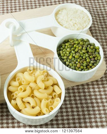 Foods High in Carbohydrate Raw Pasta Rice and Mung Beans in Plastic Measuring Spoons.