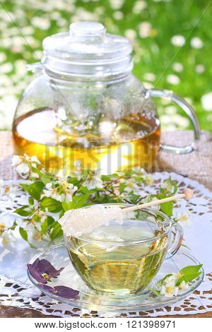 Jasmine tea and sugar swizzle stick in a glass pot and cup in front of a spring meadow