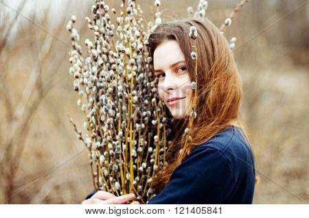 Portrait of a beautiful young girl with a huge armful of willow in hands. Young woman gardening. Por