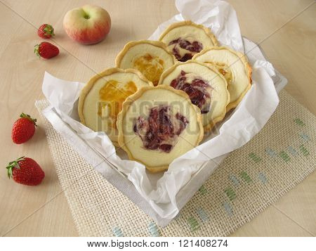 Small tartlets with fresh cheese, peach and strawberry