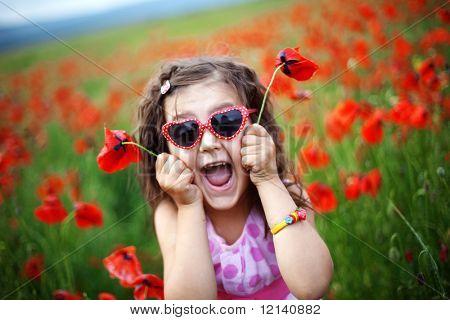 Muchacha del niño lindo en un campo de amapola