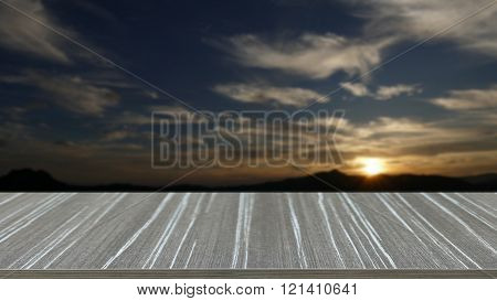 empty wooden table with sun, mountain, cloud and sky at dawn blur background