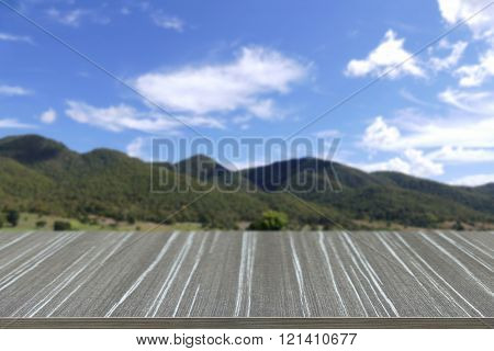 empty wooden table with mountain blur background