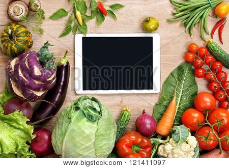 Touch screen tablet close up, kitchen table with food ingredients