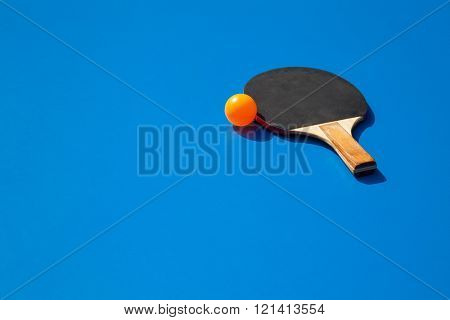 Orange ping pong ball with paddle on a blue tennis table